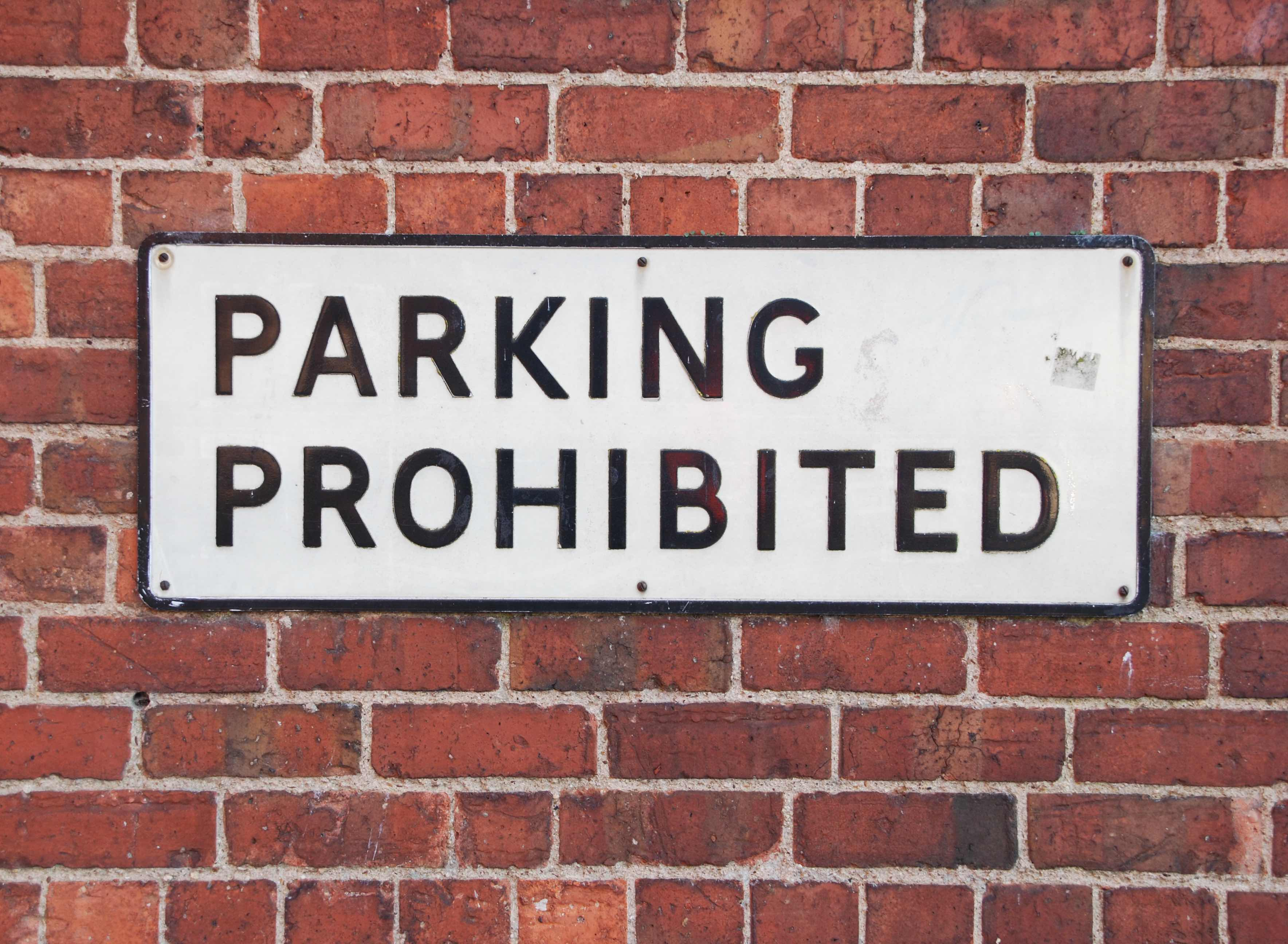 parking prohibited vintage sign at a red brick wall background