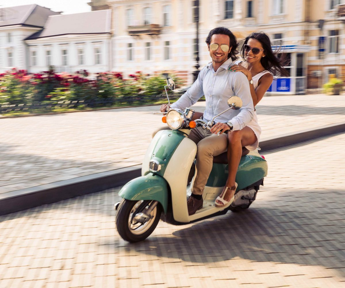 Happy couple riding on a scooter in old european town